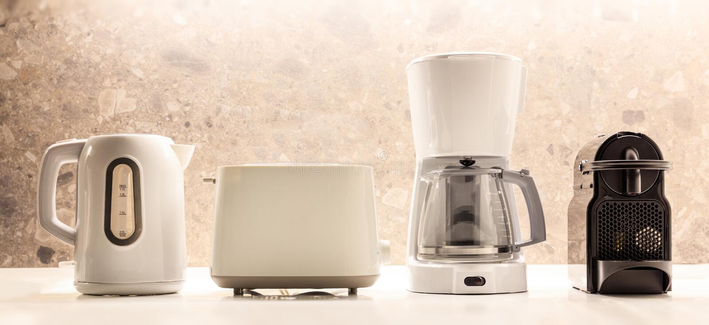 Küchenelektrogeräte auf weißer Oberfläche Bunter, unscharfer Hintergrund Schließen Sie herauf Ansicht, Details lizenzfreies stockbild