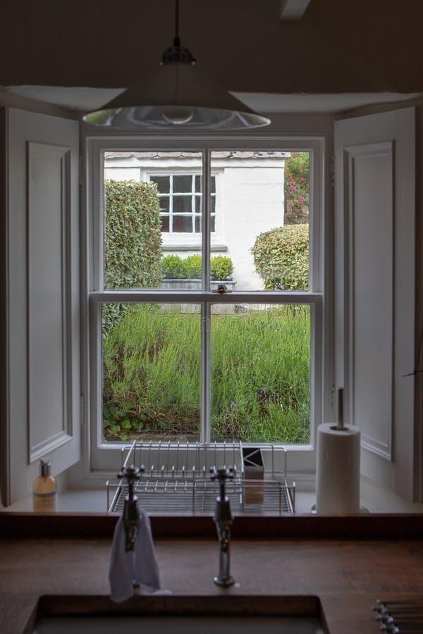 Küchenfenster in Hinterhof des Lavendels u. der Sträuche stockfoto