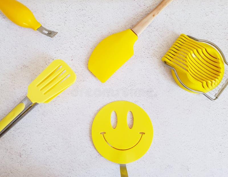 Küchengerät-Werkzeugausrüstung für die Zubereitung der Nahrung in den hellen gelben Farben lokalisiert auf weißem strukturiertem  stockbild
