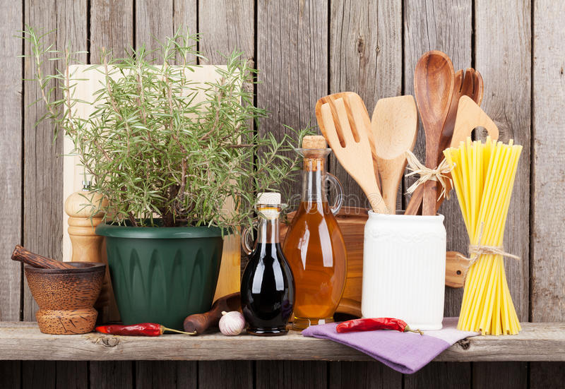 Küchengeräte, -kräuter und -gewürze auf Regal stockfotos