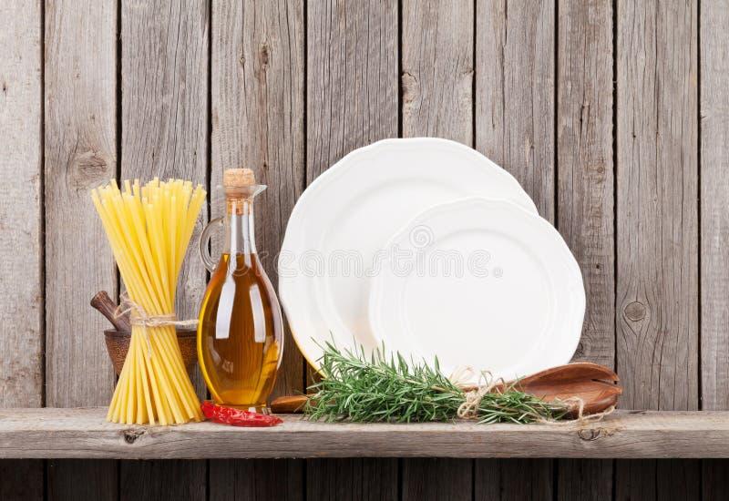 Küchengeräte, -kräuter und -gewürze auf Regal lizenzfreie stockfotografie