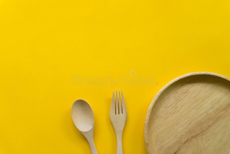 K?chengeschirrsatz des h?lzernen L?ffels und h?lzernen der Gabel lokalisiert mit gelbem Hintergrund stockfotos