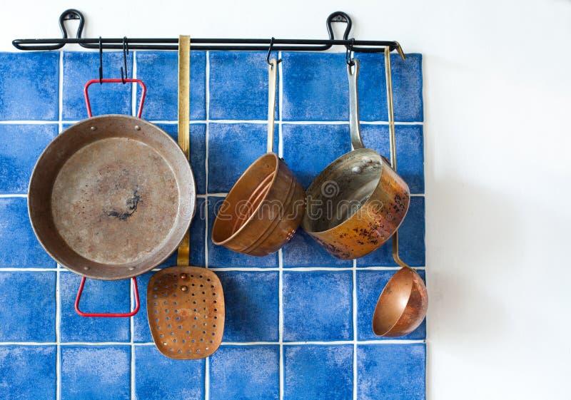 Kücheninnenraum mit Weinlesekupfergerät im altem Stil Kochgeschirrsatz Pan-Töpfe, Löffel, Abstreicheisen, das an der blauen Flies stockfotos