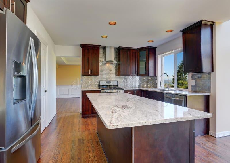 Küchenrauminnenraum mit dunkelbraunen Kabinetten mit Granitgegenspitze lizenzfreie stockfotos