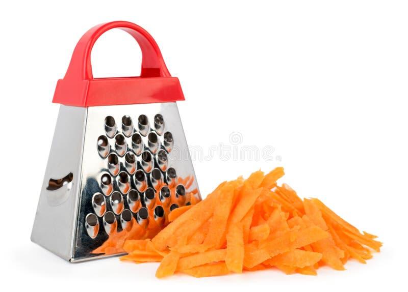 Küchenreibe und ein Bündel zerriebene Karotten auf einem weißen, lokalisiert stockfotos