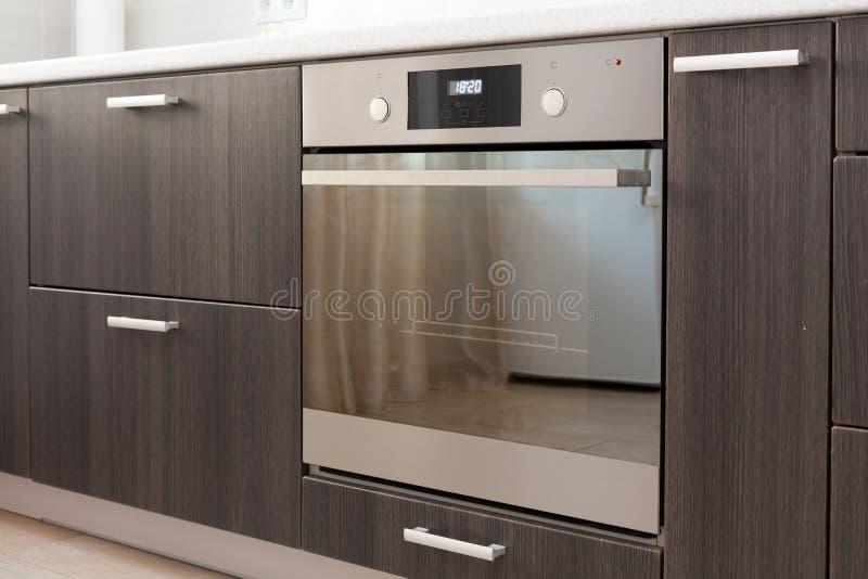 Küchenschränke mit Metallgriffen und eingebautem elektrischem Ofen stockbild