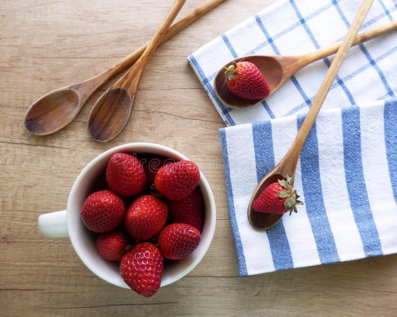 Küchenstillleben mit Erdbeeren, Löffel und Geschirrtücher auf Holztisch kochend lizenzfreie stockbilder