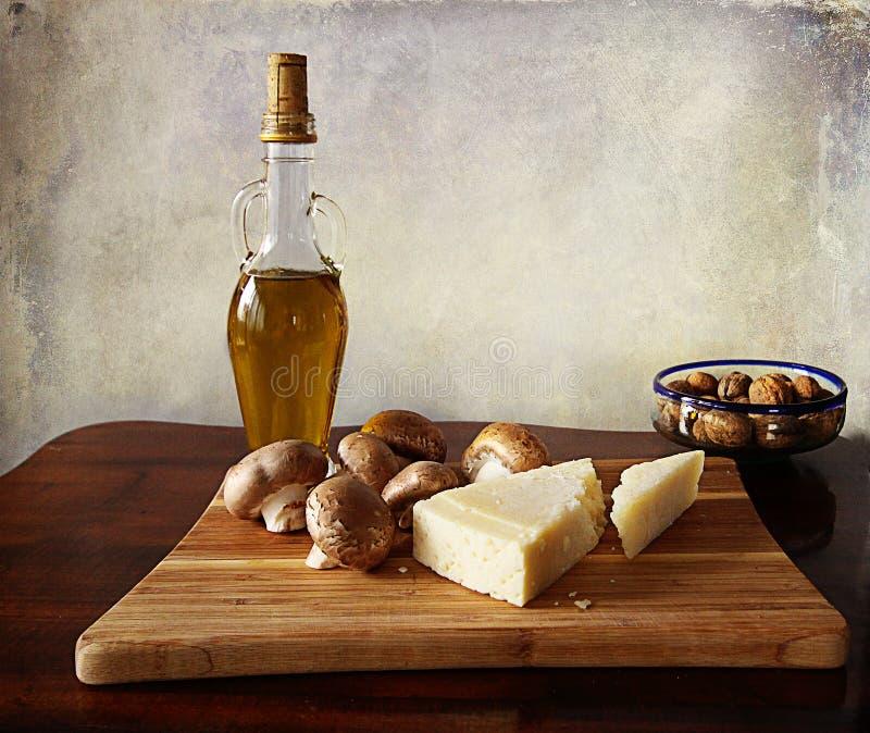 Küchenstillleben: Pilze, Walnüsse, Parmesankäse auf hölzernem Brett stockfotografie