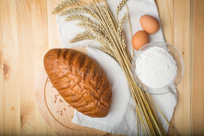 Küchenstillleben vom Mehl, von den Weizenähren, vom Brot und von den Eiern lizenzfreie stockbilder