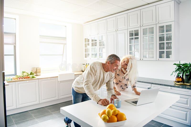Küchenszene mit den Paaren, die Computer betrachten lizenzfreies stockbild