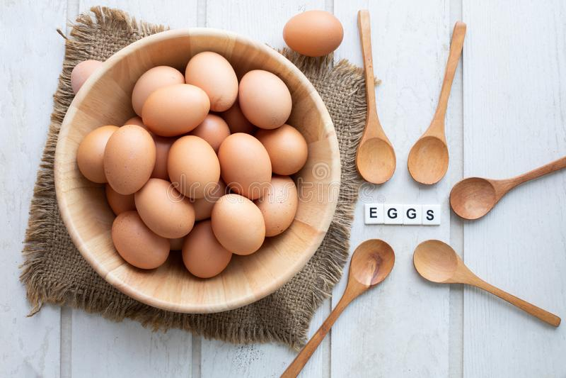 Küchentisch mit den rohen Eiern, die auf hölzernen Korb eingestellt werden und Eier simsen Buchstaben stockfotos