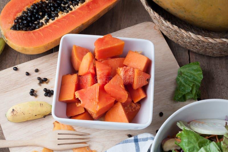Küchentisch mit geschnittener frischer Papayafrucht auf hölzerner Ausschnittboa stockfotos