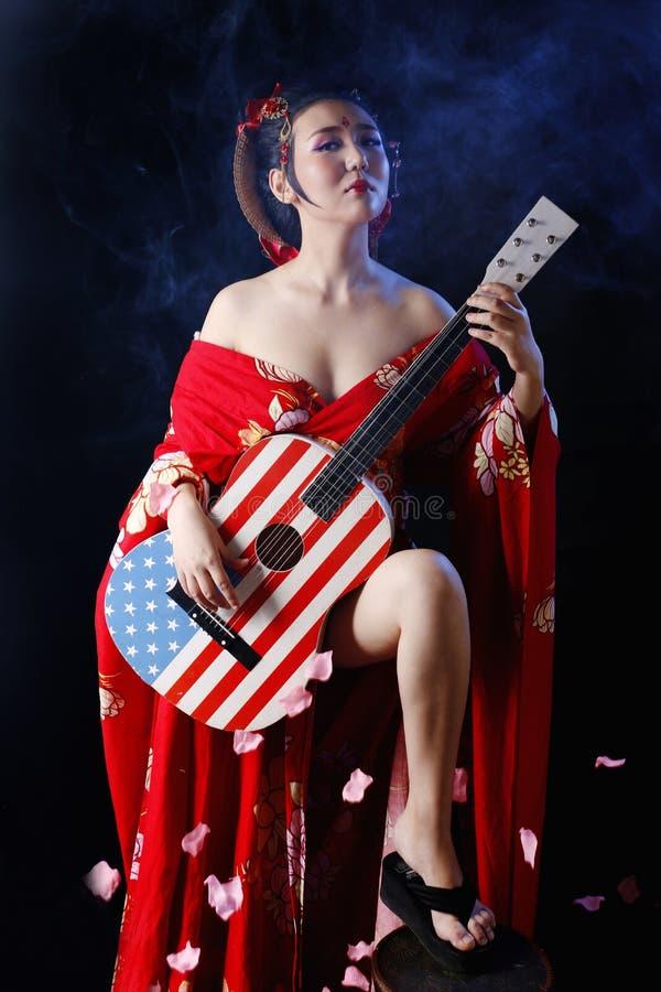 Kühle Frau, die roten Kimono trägt lizenzfreie stockfotografie