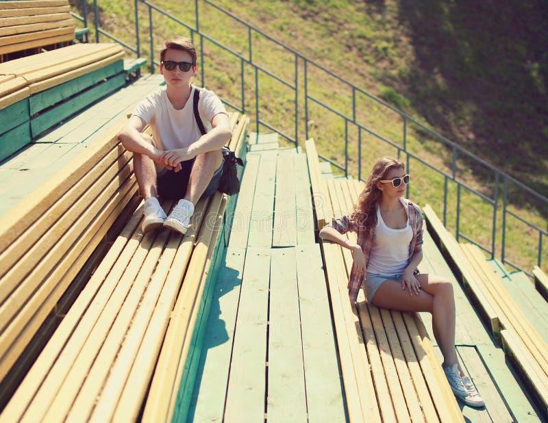 Kühle Hippie-Paare, die auf der Bank, Jugend, Jugendliche stillstehen lizenzfreie stockfotografie