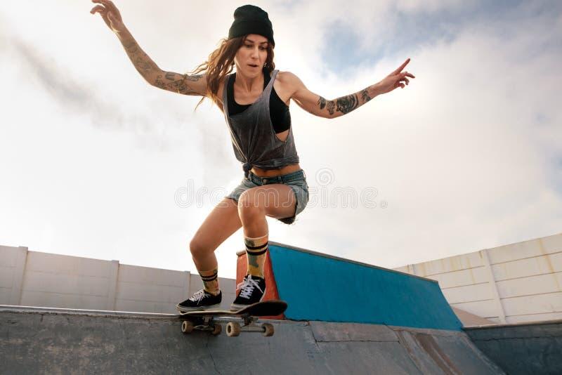 Kühle junge Frau, die am Rochenpark Skateboard fährt stockbilder