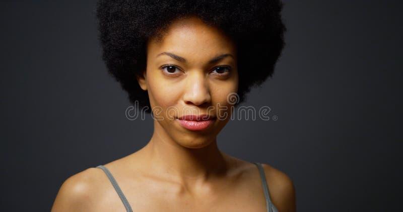 Kühle schwarze Frau, die Kamera betrachtend steht stockbild