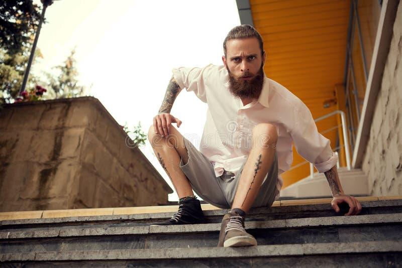Kühlen Sie das Schauen des Kerls ab, der in der Straße auf Treppe sitzt lizenzfreie stockfotografie