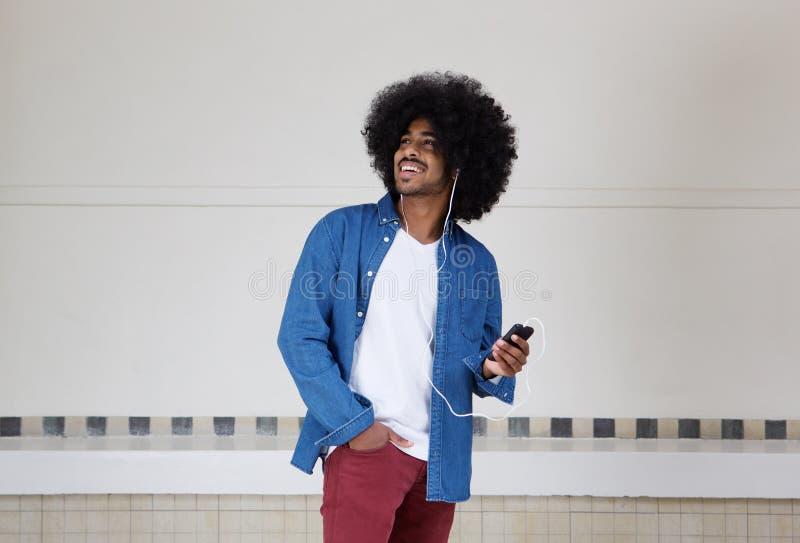 Kühlen Sie den schwarzen Kerl ab, der Musik am Handy hört stockfoto