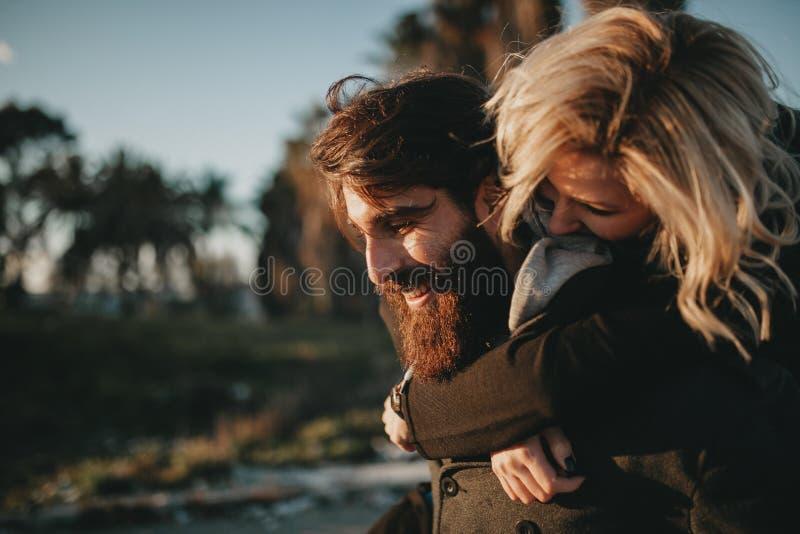 Kühlen Sie die indie Paare ab, die Spaß draußen haben, während er ihr ein Doppelpol gibt stockfotografie