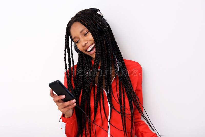 Kühlen Sie hörende Musik der jungen Afroamerikanerfrau mit Kopfhörer und Handy ab lizenzfreie stockfotos