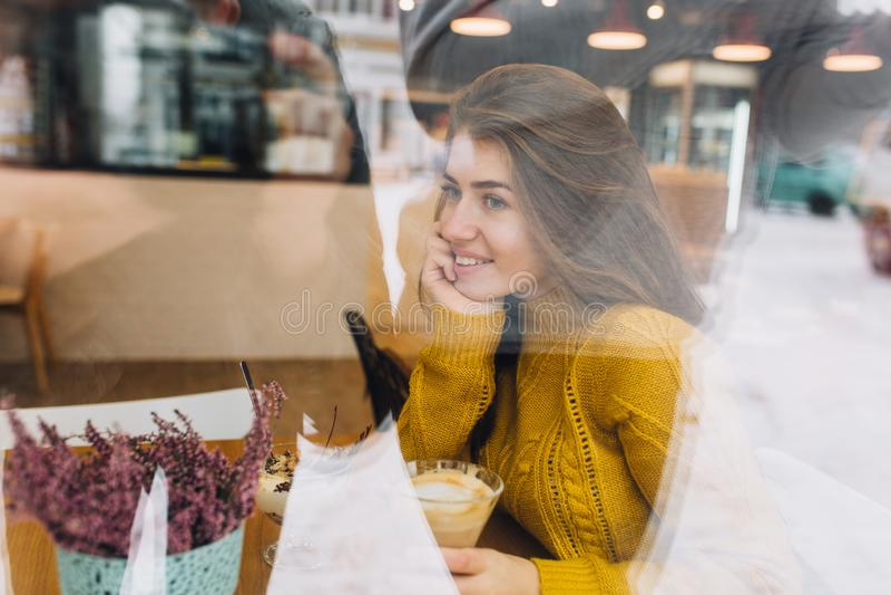 Kühlende Zeit in der Winterzeit der genossenen jungen Frau im Fenster des bequemen Cafés auf Straße Trinkender Kaffee, träumend stockbild