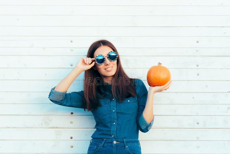 Kühler Autumn Girl in der Denim-Ausstattung und Sonnenbrille, die das Pumpen halten lizenzfreies stockfoto