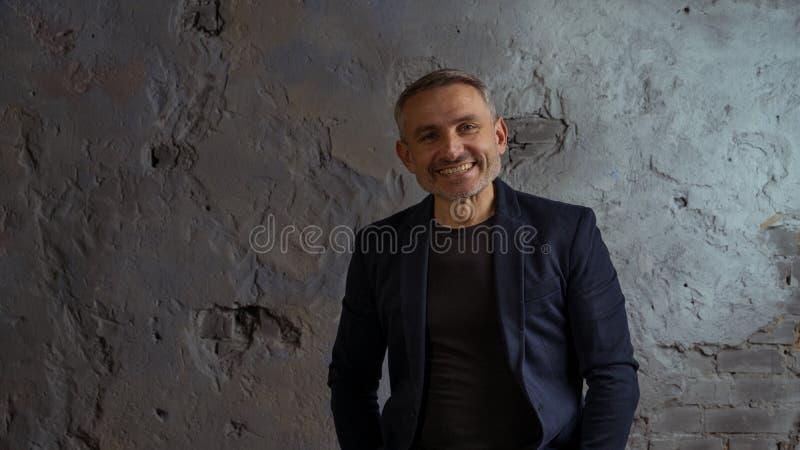Kühler Geschäftsmann mit grauer Haar- und Bartstellung auf grauem Hintergrund stockfoto