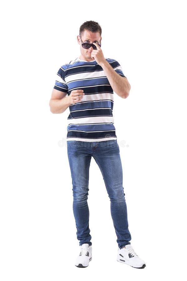 Kühler hübscher erwachsener Mann, der Sonnenbrille mit Fingerstoß justiert lizenzfreie stockbilder