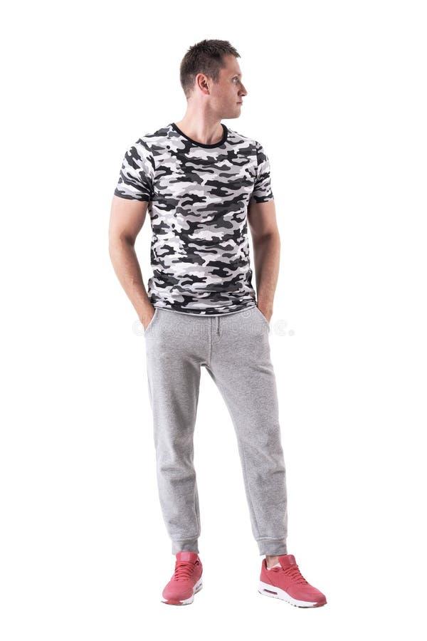 Kühler hübscher geeigneter Mann im Armeet-shirt mit den Händen in den Taschen, die weg schauen lizenzfreie stockfotos
