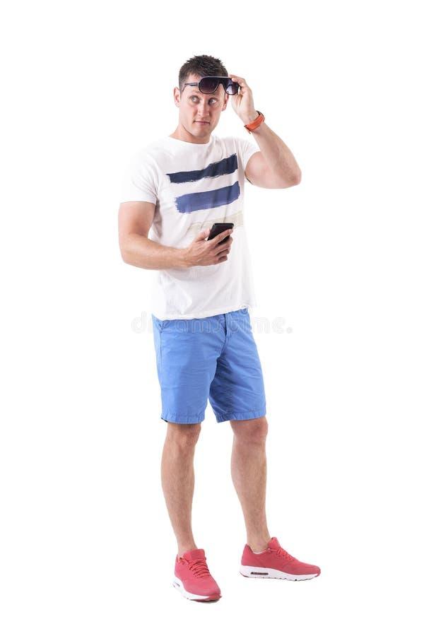 Kühler hübscher verwirrter Mann, der die Sonnenbrille und Mobiltelefon hinten schauend hält stockfotografie