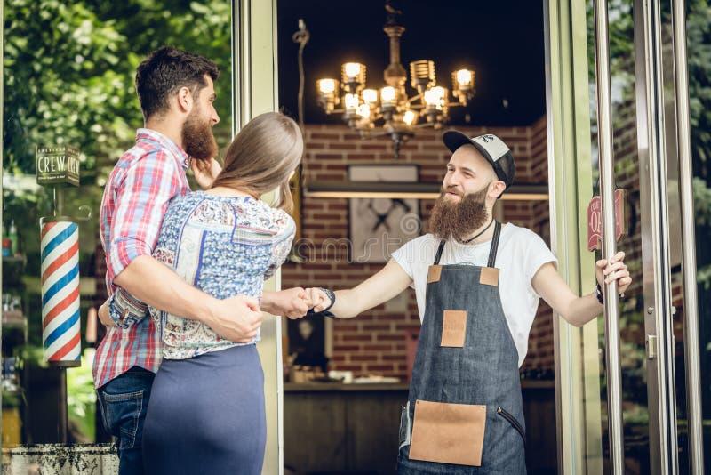 Kühler Herrenfriseur, der einem glücklichen Kunden einen Fauststoß an der Tür eines Salons gibt stockfotografie