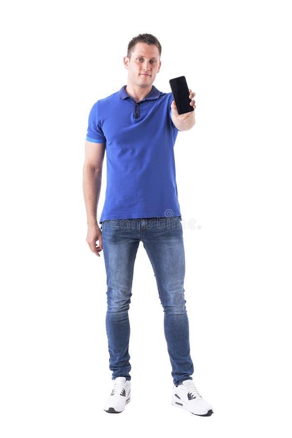 Kühler junger hübscher erwachsener zufälliger Mann, der leere Handyanzeige an der Kamera zeigt stockfotos