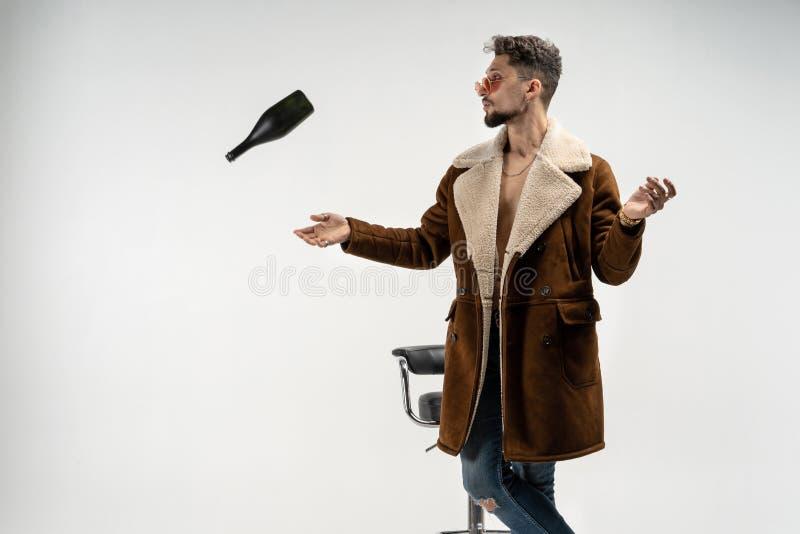 Kühler junger Mann im Mantel wirft eine Flasche im Studio stockfoto