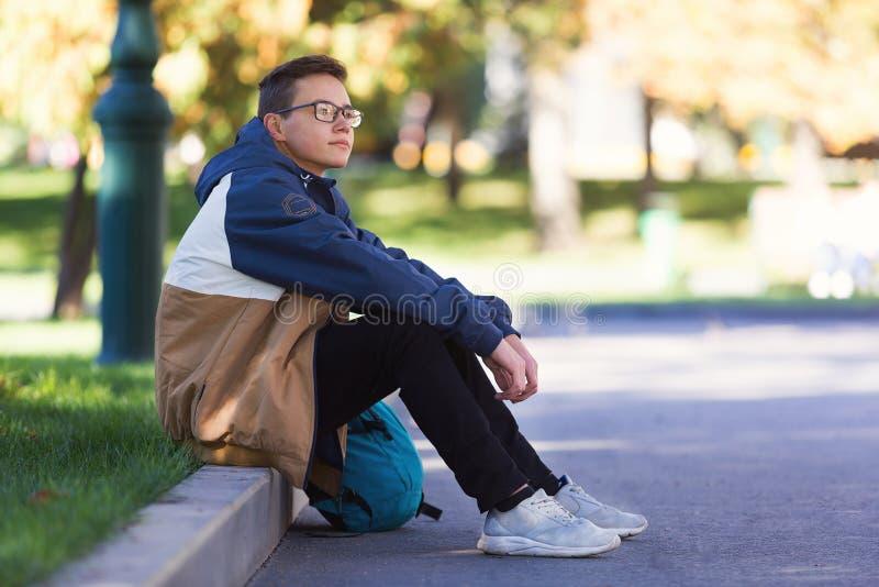 Kühler Kerl, der draußen während eines Bruches in der Klasse sitzt und sich entspannt lizenzfreie stockfotos