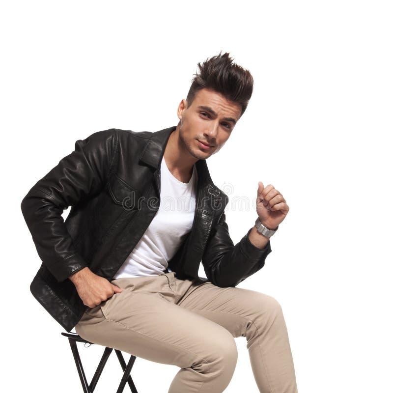 Kühler Kerl mit netter Frisur sitzt auf einem Stuhl lizenzfreies stockbild