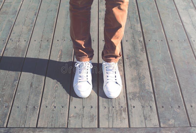 Kühler Mann des Modehippies mit weißer Turnschuhnahaufnahme steht stockbilder
