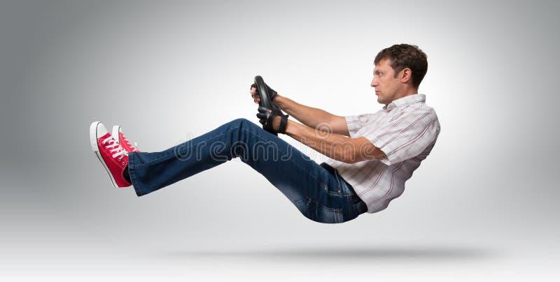 Kühler Mannautofahrer in behandschuhtem mit einem Rad, Selbstkonzept lizenzfreie stockfotos