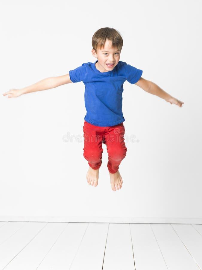 Kühler, netter Junge mit blauem Hemd und rote Hose ist das Springen hoch im Studio vor weißem Hintergrund und weißem Bretterboden lizenzfreie stockbilder