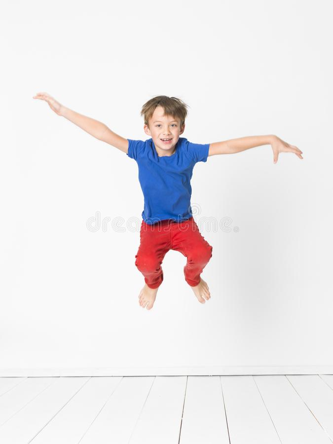 Kühler, netter Junge mit blauem Hemd und rote Hose ist das Springen hoch im Studio vor weißem Hintergrund und weißem Bretterboden stockfoto
