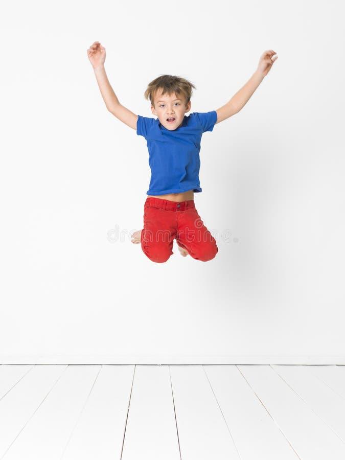 Kühler, netter Junge mit blauem Hemd und rote Hose ist das Springen hoch im Studio vor weißem Hintergrund und weißem Bretterboden stockbild