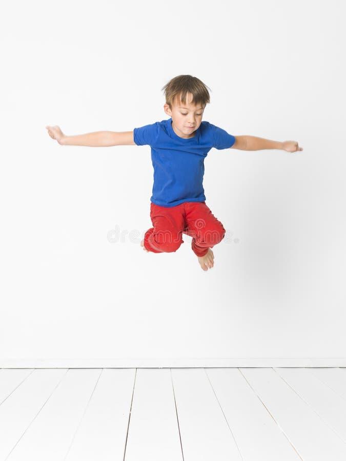 Kühler, netter Junge mit blauem Hemd und rote Hose ist das Springen hoch im Studio vor weißem Hintergrund und weißem Bretterboden lizenzfreie stockfotografie