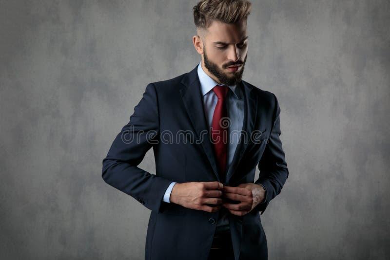 Kühler sexy junger Geschäftsmann, der unten seine Klage und Blicke knöpft stockfoto