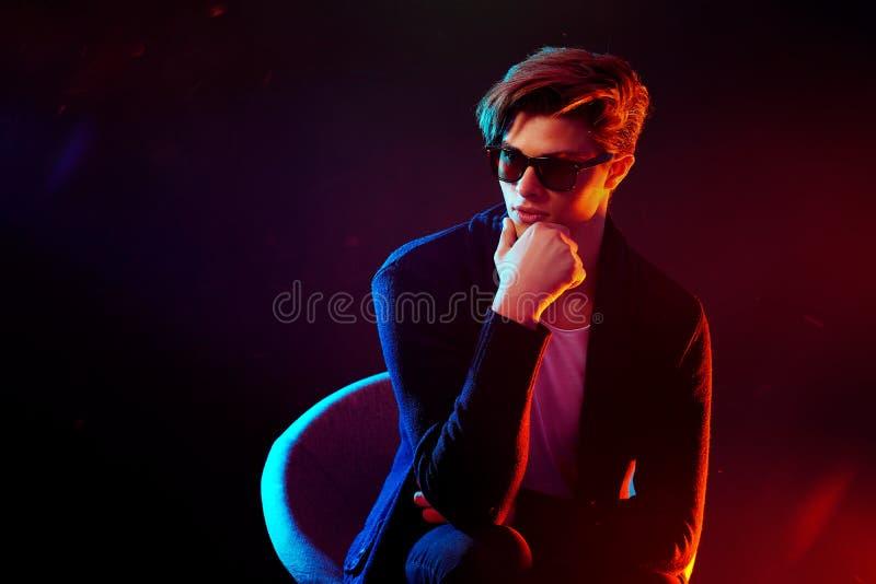 Kühler stilvoller Mann in der schwarzen Jacke und in der Sonnenbrille Männliches Modell der Haute Couture in den bunten hellen Ne stockfotografie