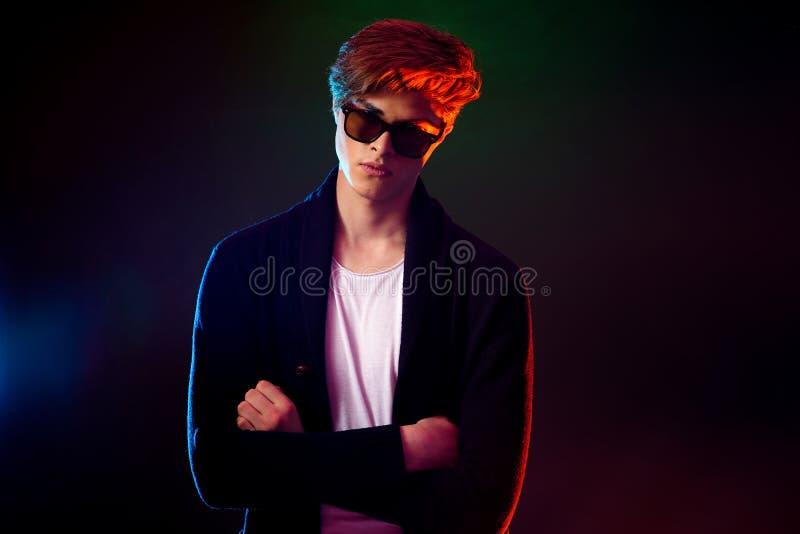 Kühler stilvoller Mann in der schwarzen Jacke und in der Sonnenbrille Männliches Modell der Haute Couture in den bunten hellen Ne stockfoto