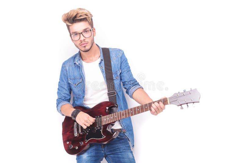 Kühler zufälliger Gitarrist, der seine rote E-Gitarre spielt lizenzfreie stockfotos