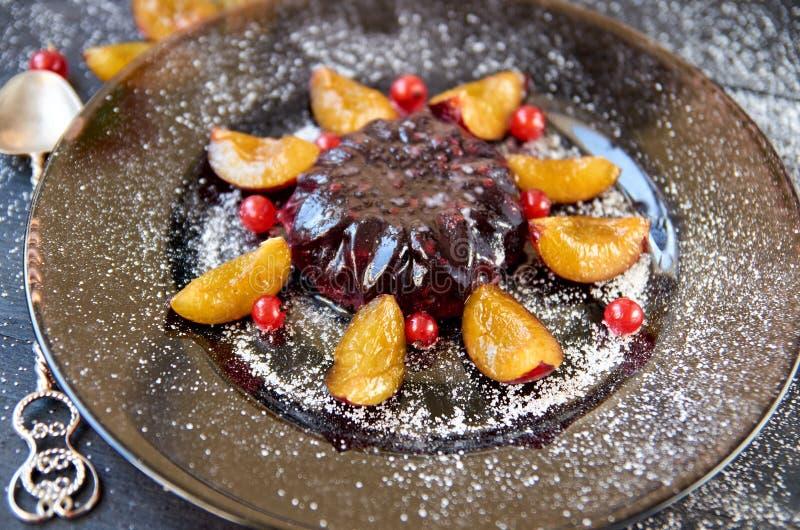 Kühles Burgunder-Gelee mit Beeren und Pulver verziert mit frischen Pflaumen, roter Johannisbeere und Silberweinleselöffel auf bra lizenzfreies stockfoto