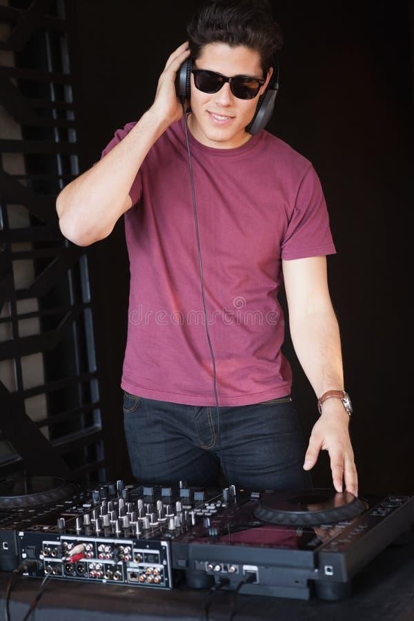 Kühles DJ in der Sonnenbrille, welche die Plattformen spinnt lizenzfreie stockfotografie