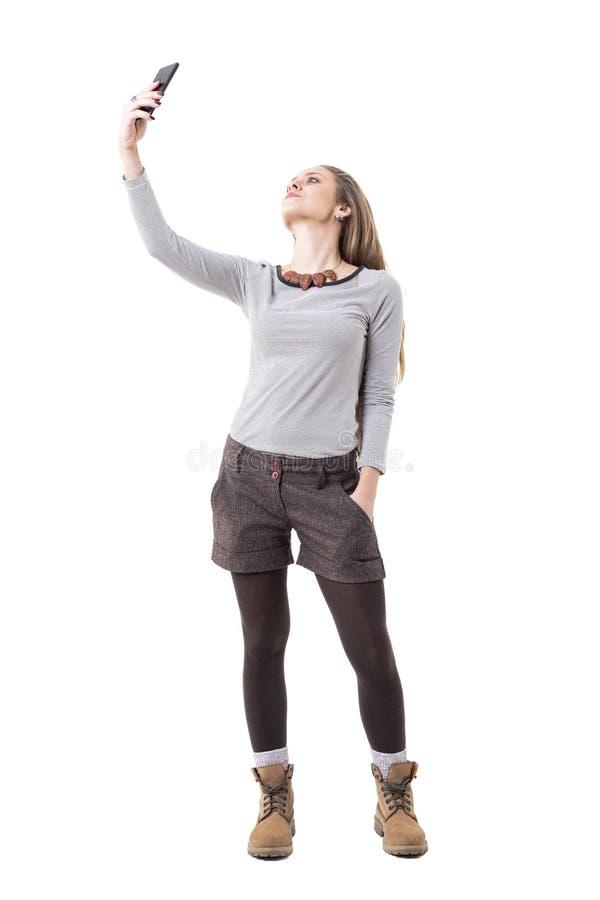 Kühles entspanntes junges stilvolles Hippie-Mädchen, das selfie mit Smartphone vom hohen Winkel nimmt stockfotografie