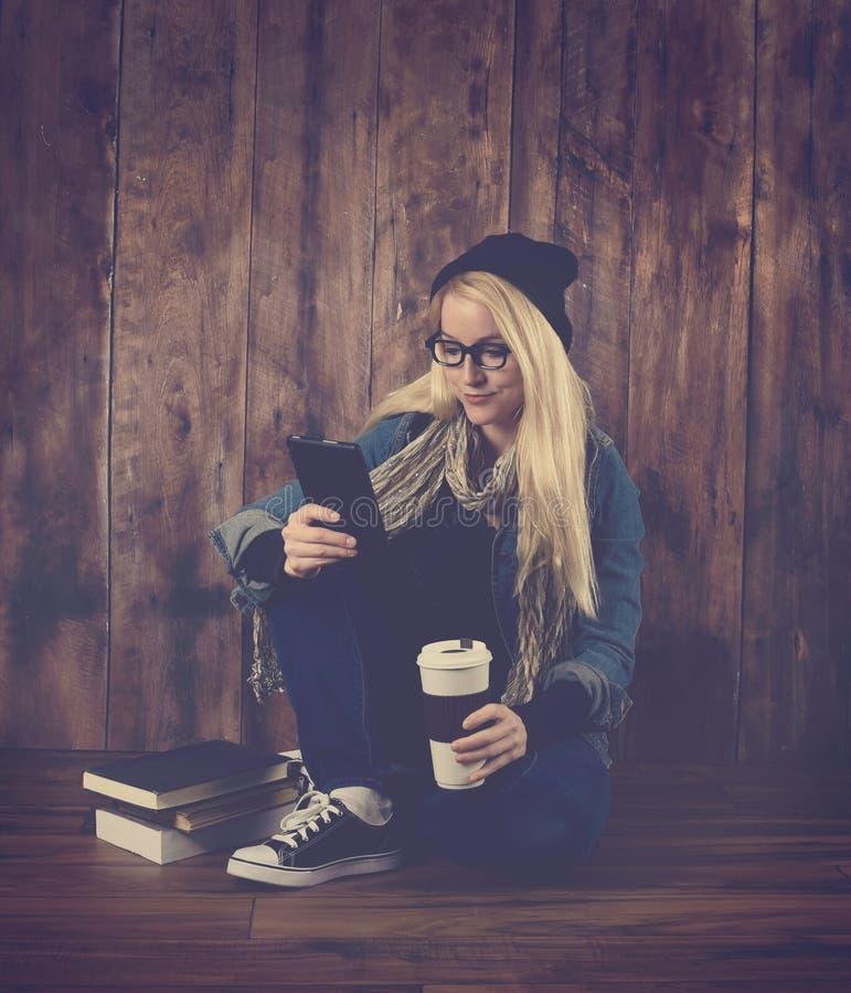 Kühles Hippie-Mädchen, das Tablet-Gerät verwendet stockfotos