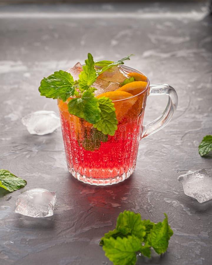 Kühles Kirschwein mit Orange und Minze in einem Glasbecher mit Eiswürfeln stockfotografie